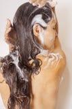 Muchacha del pelo de la espuma en la ducha Imagen de archivo