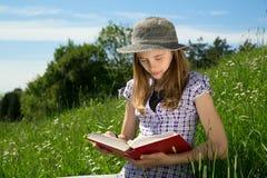 Muchacha del pelo rubio con el sombrero que estudia al aire libre en Sunny Spring Day Foto de archivo libre de regalías