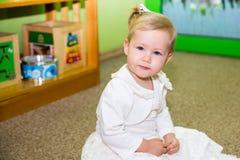 Muchacha del pequeño niño que juega en guardería en clase del preescolar de Montessori Niño adorable en sitio del cuarto de niños Imagenes de archivo