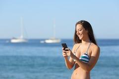 Muchacha del persona que toma el sol que usa un teléfono elegante el vacaciones de verano Imagenes de archivo