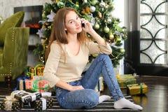 Muchacha del pintor que usa smartphone para desear Feliz Año Nuevo a los amigos Imagenes de archivo