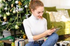 Muchacha del pintor que usa smartphone para desear Feliz Año Nuevo a los amigos Fotos de archivo