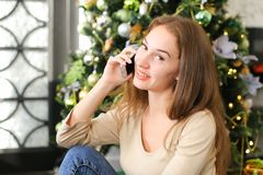 Muchacha del pintor que usa smartphone para desear Feliz Año Nuevo a los amigos Fotografía de archivo