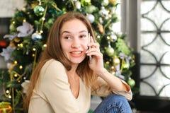 Muchacha del pintor que usa smartphone para desear Feliz Año Nuevo a los amigos Imágenes de archivo libres de regalías