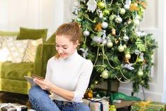 Muchacha del pintor que usa smartphone para desear Feliz Año Nuevo a los amigos Fotos de archivo libres de regalías