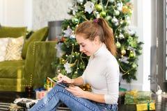 Muchacha del pintor que usa smartphone para desear Feliz Año Nuevo a los amigos Foto de archivo libre de regalías