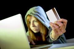 Muchacha del pirata informático que sostiene la tarjeta de crédito que viola la privacidad que sostiene la tarjeta de crédito en  Imágenes de archivo libres de regalías