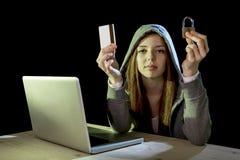 Muchacha del pirata informático que sostiene la tarjeta de crédito que viola la privacidad que sostiene la tarjeta de crédito en  Fotos de archivo