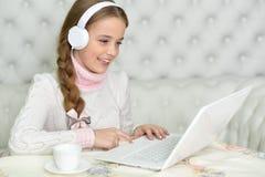 Muchacha del preadolescente con el ordenador portátil Foto de archivo