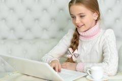 Muchacha del preadolescente con el ordenador portátil Imágenes de archivo libres de regalías