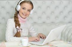 Muchacha del preadolescente con el ordenador portátil Imagen de archivo