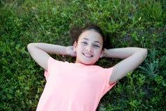 Muchacha del preadolescente con los ojos azules que mienten en la hierba Foto de archivo
