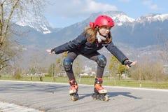 Muchacha del preadolescente en pcteres de ruedas en casco en la pista Fotos de archivo