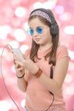 Muchacha del preadolescente que escucha la música con su smartphone, backg del bokeh Foto de archivo libre de regalías