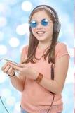 Muchacha del preadolescente que escucha la música con su smartphone, backg del bokeh Imágenes de archivo libres de regalías