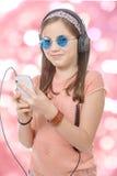 Muchacha del preadolescente que escucha la música con su smartphone, backg del bokeh Imagenes de archivo