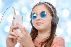 Muchacha del preadolescente que escucha la música con su smartphone, backg del bokeh Fotos de archivo libres de regalías