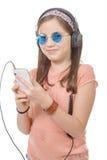 Muchacha del preadolescente que escucha la música con su smartphone, en blanco Foto de archivo