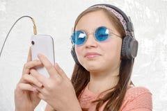 Muchacha del preadolescente que escucha la música con su smartphone, en blanco Imagen de archivo