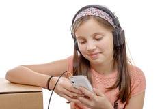 Muchacha del preadolescente que escucha la música con su smartphone, en blanco Imágenes de archivo libres de regalías