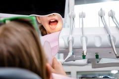 Muchacha del preadolescente que mira sus dientes en el espejo en cl?nica dental pedi?trica foto de archivo libre de regalías