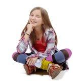 Muchacha del preadolescente que se sienta a piernas cruzadas en el piso Foto de archivo libre de regalías