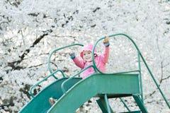 Muchacha del preescolar que lleva el sombrero rosado de la chaqueta y del cubo que desliza abajo la vieja diapositiva del patio Imágenes de archivo libres de regalías