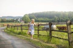 Muchacha del pueblo con un bolso de la leche y del pan que pasan a través de los campos con el pasto de vacas Vida rural del vera fotografía de archivo