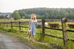 Muchacha del pueblo con un bolso de la leche y del pan que pasan a trav?s de los campos con el pasto de vacas Vida rural del vera imagen de archivo libre de regalías