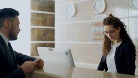 Muchacha del recepcionista en el hotel que habla con el hombre de negocios llegado sobre enregistramiento y que da la llave elect almacen de video