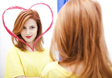 Muchacha del Redhead cerca del espejo Imágenes de archivo libres de regalías