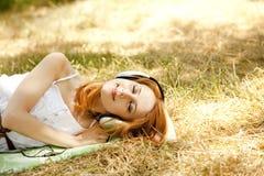 Muchacha del Redhead con los auriculares en el jardín. Imagen de archivo