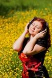 Muchacha del Redhead con los auriculares que escucha la música Fotos de archivo libres de regalías