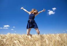 Muchacha del Redhead en el campo de trigo en día de verano. Foto con el bokeh en b Foto de archivo