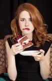 Muchacha del Redhead que come secretamente la torta. Imágenes de archivo libres de regalías