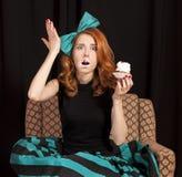 Muchacha del Redhead que come secretamente la torta. Imagen de archivo