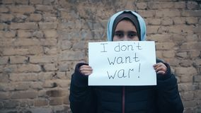 Muchacha del refugiado con una inscripción en una hoja blanca almacen de video
