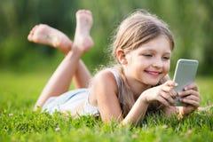 Muchacha del retrato que miente en parque y que juega con el teléfono móvil Fotografía de archivo