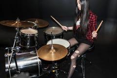 Muchacha del rock-and-roll que juega música de heavy con los tambores fijados Imagen de archivo