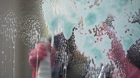 Muchacha del servicio de la limpieza que aplica agentes de limpiamiento a todas las superficies de cristal almacen de metraje de vídeo