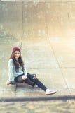 Muchacha del skater del inconformista con el monopatín al aire libre en el skatepark Imagen de archivo libre de regalías
