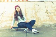 Muchacha del skater del inconformista con el monopatín al aire libre en el skatepark Imágenes de archivo libres de regalías