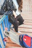 Muchacha del skater del inconformista con el monopatín que se coloca al aire libre Fotografía de archivo libre de regalías