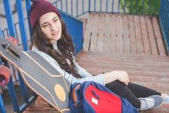 Muchacha del skater del inconformista con el monopatín que se coloca al aire libre Imagen de archivo libre de regalías