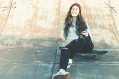 Muchacha del skater del inconformista con la sentada al aire libre del monopatín en el skatepark Fotografía de archivo libre de regalías