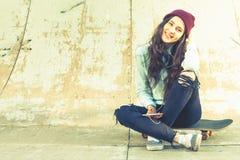 Muchacha del skater del inconformista con la sentada al aire libre del monopatín en el skatepark Fotos de archivo