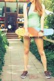 Muchacha del skater del primer con el monopatín al aire libre en el skatepark Fotos de archivo