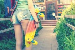 Muchacha del skater del primer con el monopatín al aire libre en el skatepark Fotografía de archivo