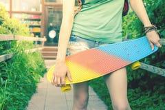 Muchacha del skater del primer con el monopatín al aire libre en el skatepark Imagenes de archivo