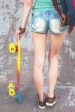 Muchacha del skater del primer con el monopatín al aire libre en el skatepark Imagen de archivo